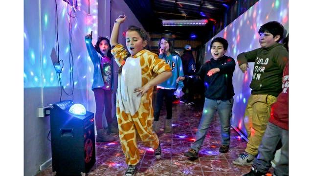 Selenna, luciendo un traje de jirafa, baila con otros niños al final de un taller de identidad de género en un centro comunitario en Santiago de Chile.