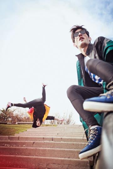 Hakim (atrás): chaleco inflado (Nexxt en Scandinavian), campera hoodie (The Northface), remera deportiva (Adidas Originals), joggin (Nike), zapatillas deportivas (Adidas Originals). Chris: parka oversize (Adidas Originals), campera running reflex (The Northface), remera estampada (Adidas Originals),. Foto: Osky Sorairez