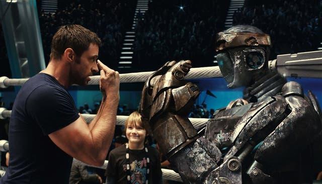 Charlie Kenton (Hugh Jackman) y Atom, el robot sparring que pasa del fango a la gloria gracias a Max Kenton (Dakota Goyo, en el centro)