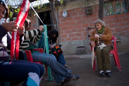 Paula en el patio de su casa junto a su familia, todos tejen y ayudan en la labor. Foto: LA NACION / Rodrigo Néspolo/Enviado especial