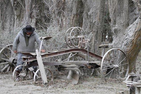 Un hombre observa la maquinaria agrícola cubierta de ceniza; en Bariloche ya comenzaron las tareas de limpieza. Foto: AFP