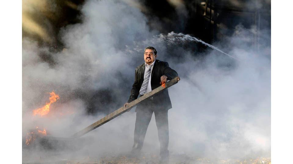 Empleado de seguridad de la Cámara de Diputados intenta apagar el fuego de cubiertas frente al edificio, después de la movilización de la Mesa de Unidad Sindical en Río Gallegos. Santa Cruz, 26 de mayo 2016. Foto: Francisco Muñós