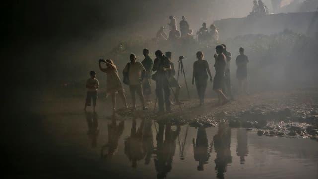 Espectadores envueltos en humo por las bengalas mientras miran a los competidores