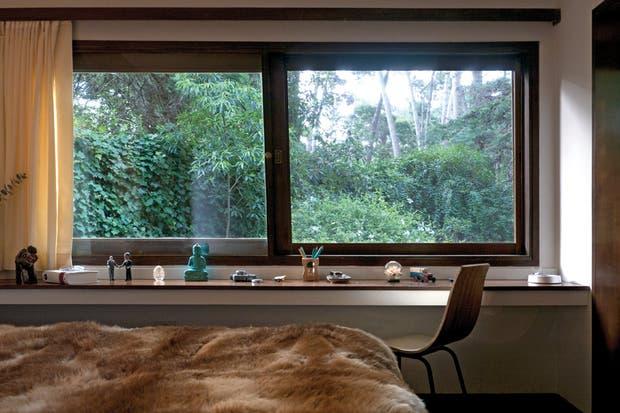 El ventanal corredizo con marco de madera genera una agradable sensación de frescura al incorporar el verde en el dormitorio principal.