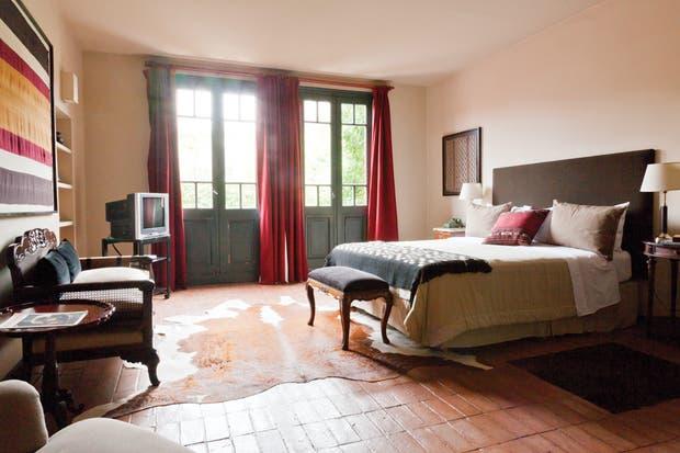 Epígrafe (515) Esta habitación se destaca por la alfombra de cuero de vaca y la biblioteca empotrada, llena de vasijas y adornos de alfarería..
