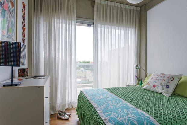 Sobre la manta de tejido grueso verde agua, pie de cama bordado traído de México y almohadón floreado de Ikea. Para tamizar la luz, etéreas cortinas de lino claro.  Foto:Living /Daniel Karp