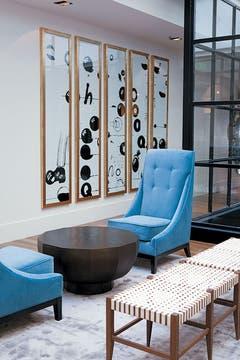 Sillones individuales y banquetas compatibles con los cuadros rectangulares que cuelgan de las paredes. Foto: Adela Aldama