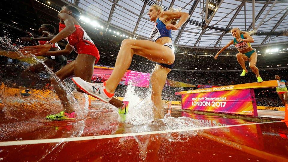 3000 metros de corridas de obstáculos Los competidores saltan sobre un obstáculo de agua. Foto: Reuters