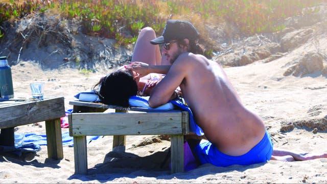 En la playa, toman mate, nadan en el mar y se sacan fotos.