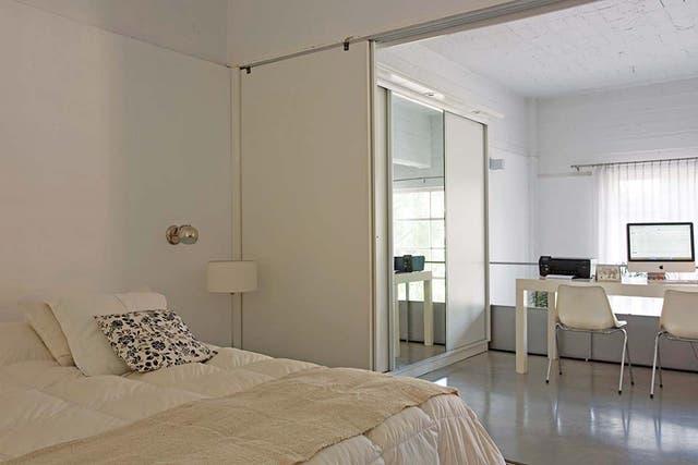La cama está vestida con acolchado y almohadones traídos la casa de Pilar. Los apliques cromados ya estaban en el dúplex
