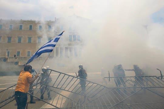 Un hombre con una bandera se enfrenta con la policía antidisturbios. Foto: Reuters