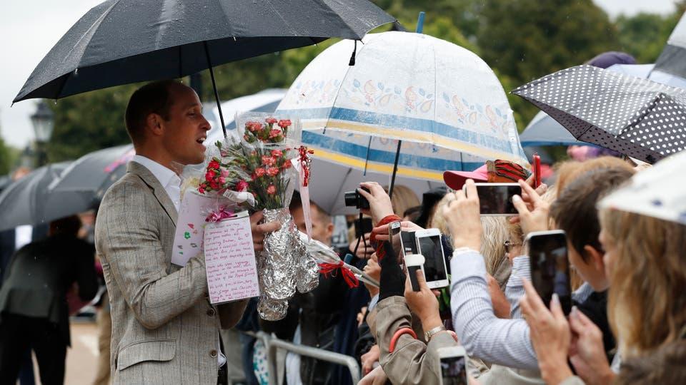 El Príncipe William toma flores del publico para colocarlos entre los tributos a su madre, la Princesa Diana, en las puertas del Palacio de Kensington . Foto: AP / Kirsty Wigglesworth