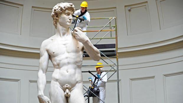 Dos operarios especializados trabajan sobre la escultura