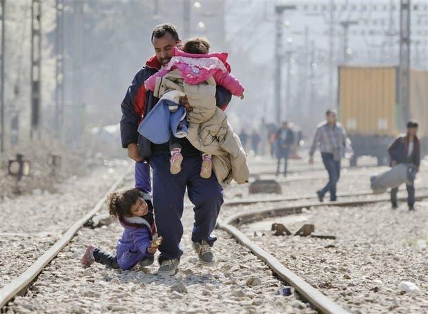 En Idomeni, Grecia, cerca de la frontera con Macedonia, un refugiado camina con sus hijos por la vía férrea