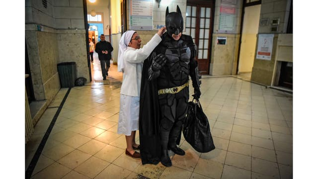 La hermana Adriana ayuda a Batman con su capa antes de visitar a los niños