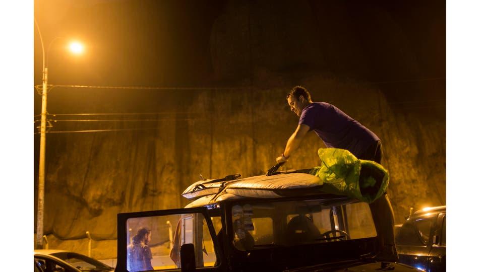 Mario Razzeto acomoda la tabla en el techo de su auto. Foto: AP / Rodrigo Abd