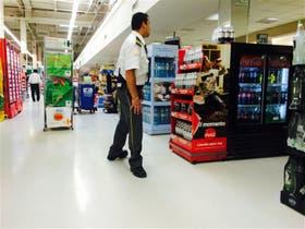 Personal de una empresa de seguridad controla las góndolas de un local Carrefour, en Vicente López