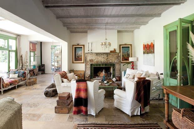 El living, con paredes en off white, combina detalles en rojo. El techo original, de pino tea, fue mantenido en el sector central, mientras que en el otro extremo debió ser cortado para integrar el sector del altillo al living..