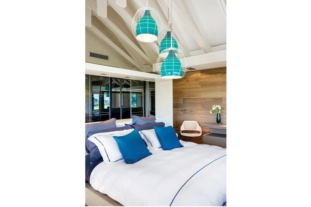 Como la suite principal está en el piso superior, la trama que crean las vigas del techo, pintadas de blanco brillante, son un elemento de fuerte presencia..