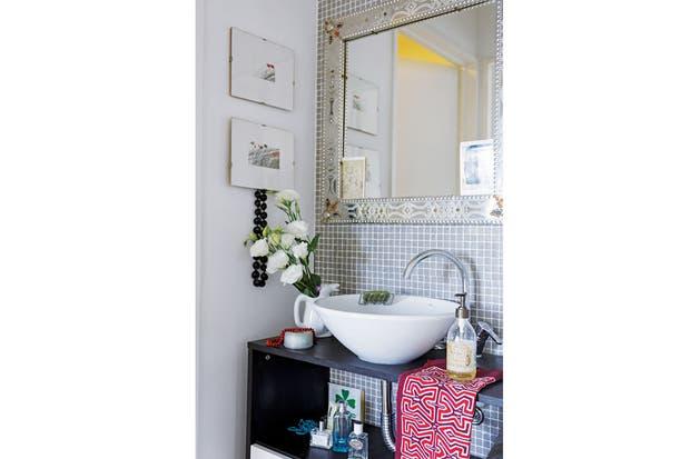 Puerta mediante, Laura separó el vanitory del resto del baño y lo equipó con un mueble de MDF oscuro con bacha redonda. El pingüino de cerámica siempre tiene flores frescas.  Foto:Living /Daniel Karp