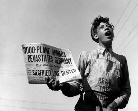 """Un chico vocea el diario, que dice: """"3000 aviones devastan Alemania"""" (1944). Foto: Dorothea Lange"""