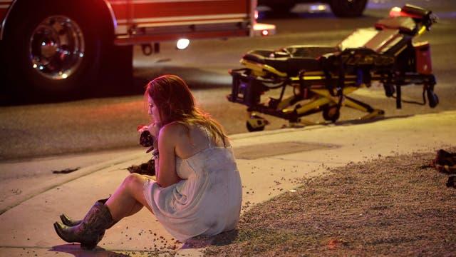 Una mujer aturdida tras el tiroteo logró escapar y permanece sentada en las afueras del Strip de Las Vegas, donde se realizó el recital