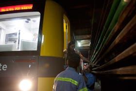 Una mujer baja a las vías, con la ayuda de empleados de Metrovías