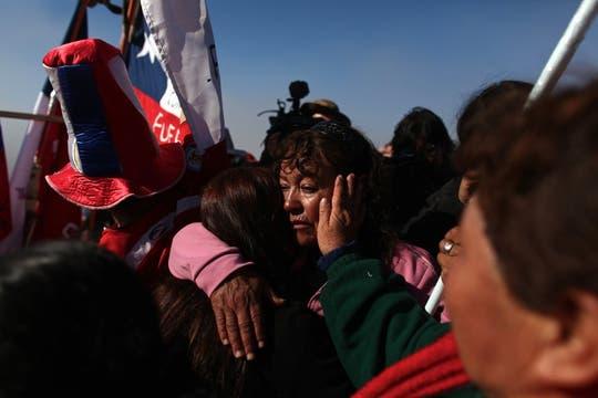 Familiares y amigos emocionados luego de que la preforadora T-130 llegó al refugio de los mineros. Foto: LA NACION / Aníbal Greco
