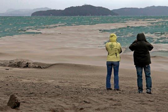 Dos personas toman fotografías del lago Nahuel Huapi cubierto de ceniza volcánica. Foto: AP