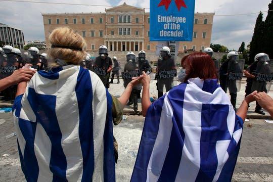 Manifestantes envueltos en banderas permanecen parados frente a la policía que custodia el Parlamento. Foto: Reuters