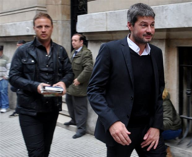 Matías Lammens sale de la reunión, secundado por Hernán Lewin, presidente de Temperley