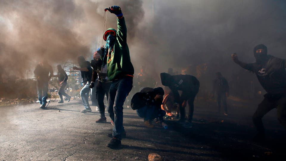 Manifestantes palestinos se enfrentan con tropas israelíes cerca de un puesto de control israelí en la ciudad cisjordana de Ramallah