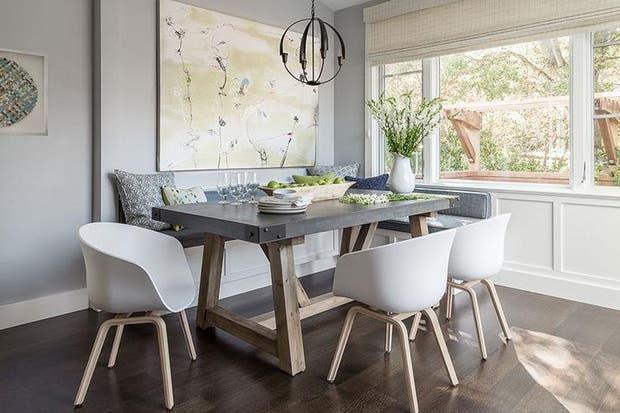 en este rincn un comedor vestido con pisos de madera de roble la mesa de esttica industrial se combin con tres sillas blancas de plstico y un banco