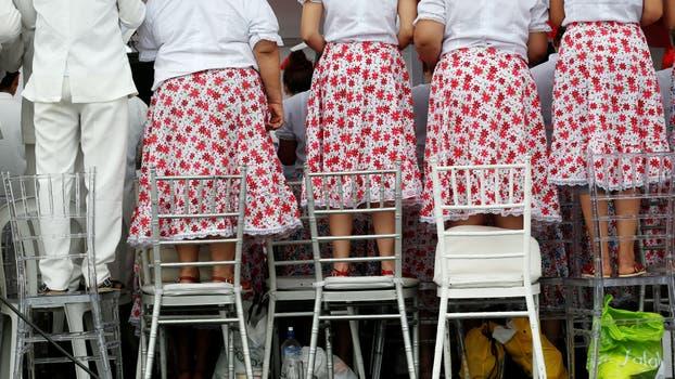 Miembros del coro parados sobre sillas mientras el Papa llega al predio. Foto: Reuters / Stefano Rellandini