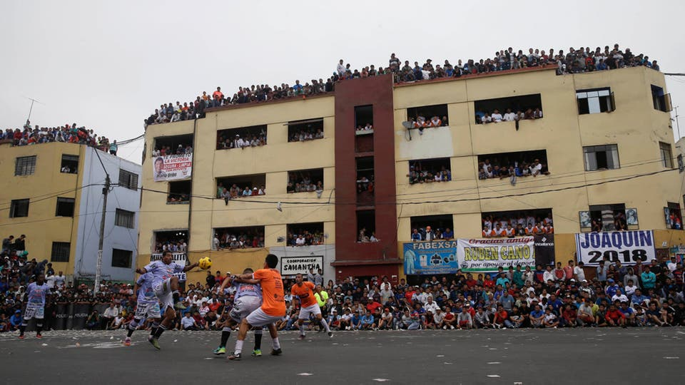 Residentes se agolpan en los balcones de un edificio para ver a los equipos de fútbol