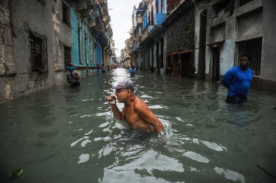 Un cubano atraviesa una calle inundada en La Habana. Foto: AFP