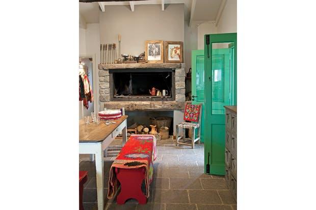 El comedor diario armado con una mesa vieja y bancos pintados de rojo se ubicó junto a un fogón con frente de piedra. Sostiene la puerta una silla santiagueña con manta bordada del NOA..