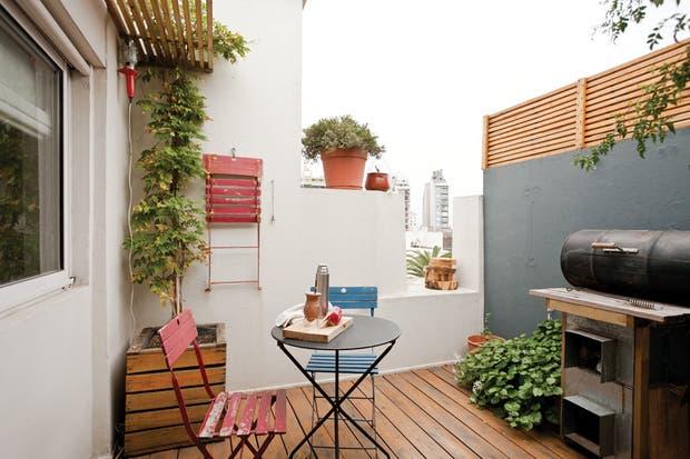 La terraza es un lugar de descanso y reuniones. Mesa Quilmes (Mercado de Pulgas Dorrego) con sillas de hierro y madera pintada (Morph). Las pérgolas, el panel divisorio y el deck se hicieron con madera de eucalipto en bruto..