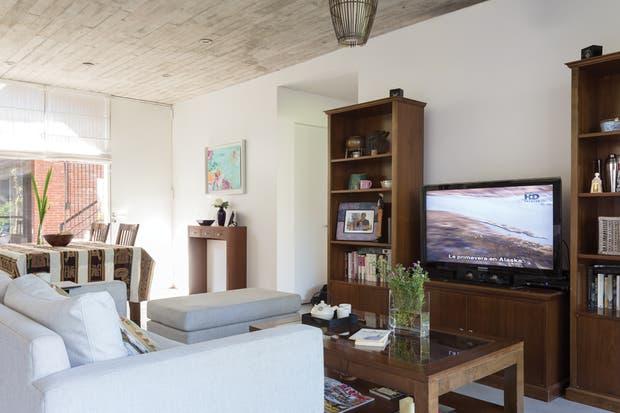 De madera oscura y a tono con el resto de los muebles, el mueble de TV incorpora también espacio de guardado.  /Daniel Karp