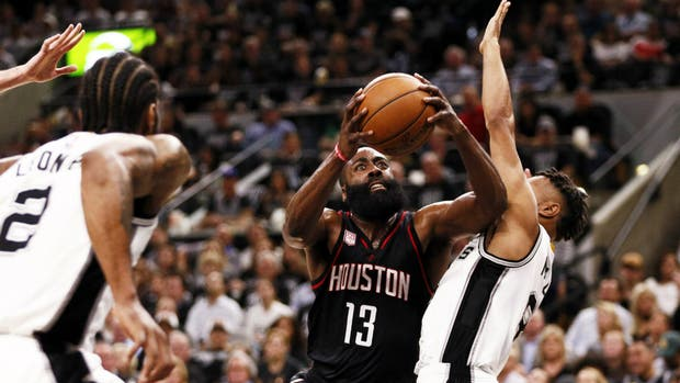 James Harden intenta superar a Patty Mills; Kawhi Leonard observa