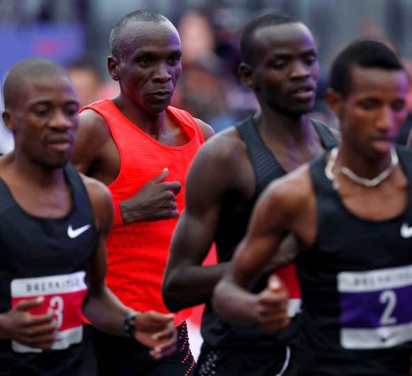 """El keniata Eliud Kipchoge (en el centro, con musculosa roja), detrás del grupo de """"liebres"""", buscando la marca de las 2 horas"""
