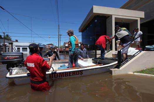 Los bomberos llevan en bote a las personas al hospital. Foto: LA NACION / Ricardo Pristupluk