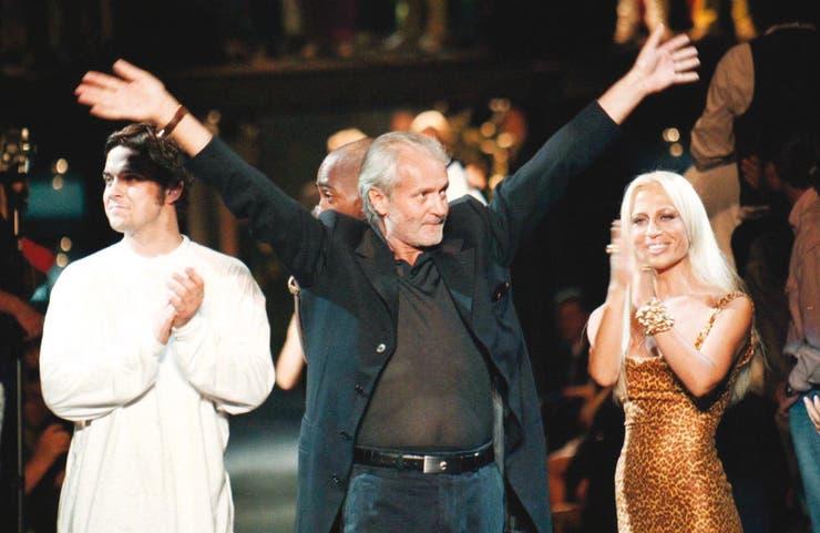 Aplaudido por su hermana Donatella y el músico Robbie Williams, Gianni disfruta del éxito en uno de sus últimos desfiles, en junio de 1996, en Miami Beach; frente a su casa de esa ciudad fue asesinado el 15 de julio de 1997