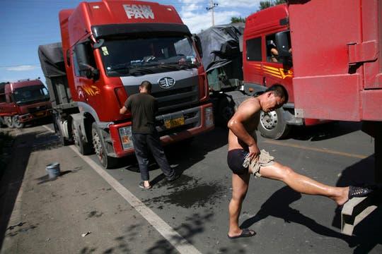 Un camionero que ya lleva dos días atascado en el embotellamiento se lava mientras continúa con la densa espera, la contrucción de un camino generó 100 km de cola y 10 días de atasco de tránsito. Foto: AP