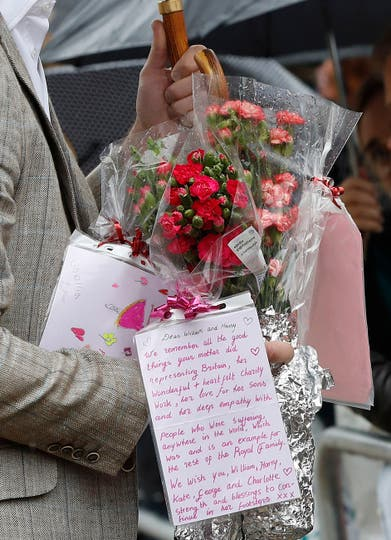 El Príncipe William de Gran Bretaña toma flores y notas del público que luego colocó entre los tributos florales y pictóricos a su madre, la princesa Diana, en las puertas del Palacio de Kensington . Foto: AP / Kirsty Wigglesworth
