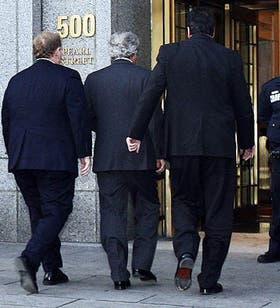Bernie Madoff (centro) ingresa en los tribunales escoltado por oficiales federales