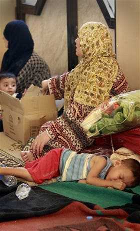 Un grupo de refugiados descansa en la frotera siria con Irak