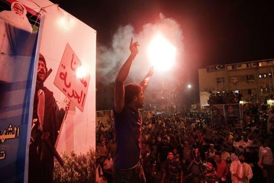 Un rebelde libio sostiene una bengala mientras miles se reunen en Benghazi, Libia, en apoyo al avance de la insurgencia en Trípoli.