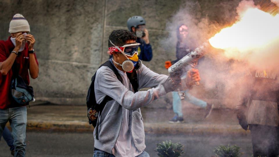 Un manifestante dispara un mortero casero en una manifestacion en Caracas. Foto: Reuters / Carlos Garcia Rawlins