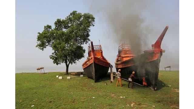 Trabajadores reparan un barco a orillas del río Ganges en Hanra, al sur de Kolkata